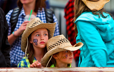 Young spectators watch the bull riding and bronc busting at the Calgary Stampede.