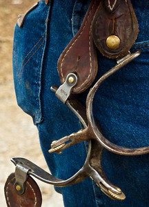 A cowboy keeps his spurs -- made in Korea -- hanging from his belt.
